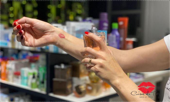 Mulher aplicando perfume no pulso do braço direito