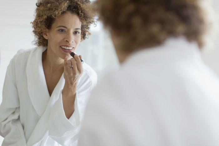 Mulher madura se maquiando em frente ao espelho